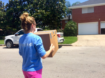Woman carrying a cardboard box across the street to a house