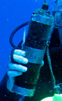 A closeup up view of an acoustic receiver in the hand of a diver.  The receiver is about the size and shape of a 1 liter bottle.