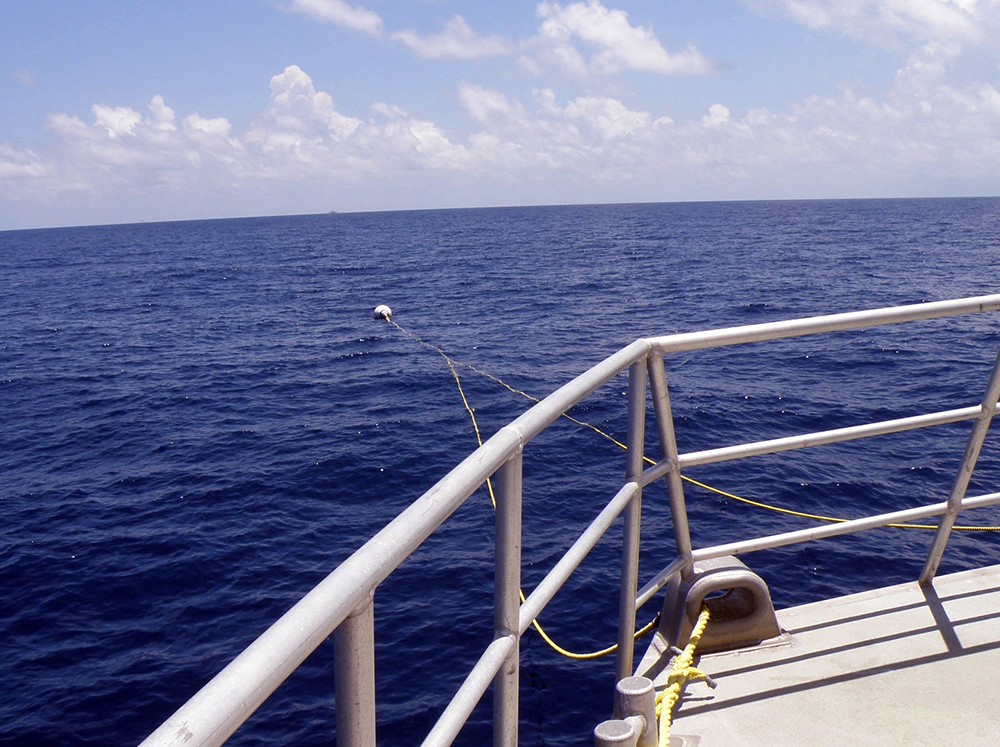 Looking over the bow railing of a boat at the lines attaching it to a mooring buoy in the water