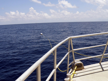 Looking past the front railing of a boat to the mooring buoy floating on the surface of the ocean.