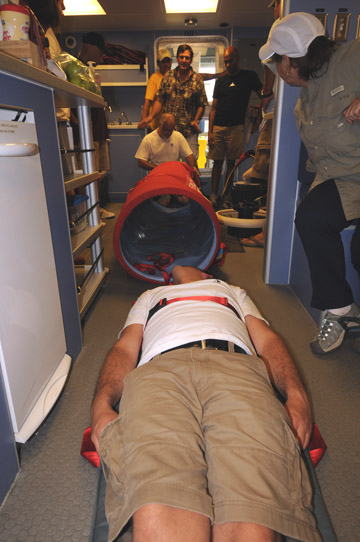 A man lying strapped to a stretcher on the floor of the R/V Manta.  The man's legs are facing toward the viewer and beyond his head is a long orange tube which the stretcher will be placed inside of.