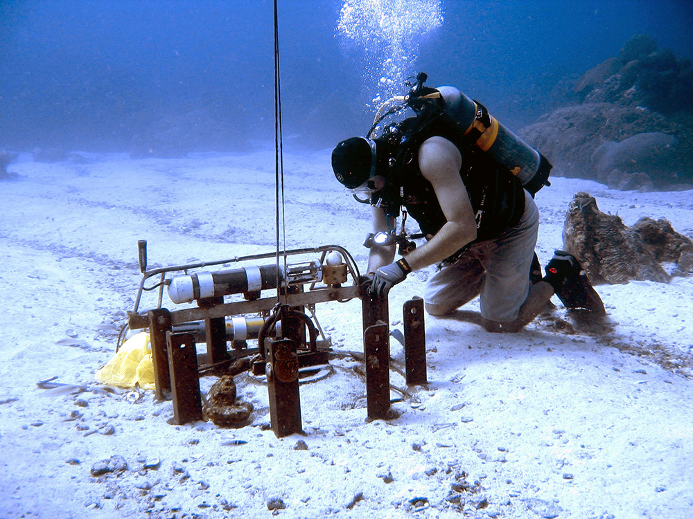 A diver kneeling next to equipment on the sea floor in a sand patch