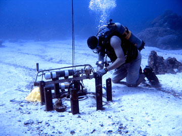 Tubular data instruement attached to the upright pieces of a large railroad wheel partly buried in the sandy sea floor.  A diver is kneeling next to the equipment.