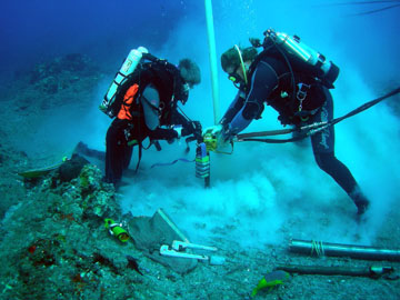 Two divers, one on each side, pushing the hydraulic drill into the rock at Stetson Bank.