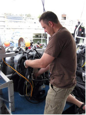 A man checking on his scuba gear as it sits on the dive bench of the R/V Manta.
