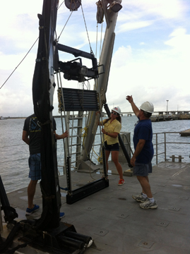 Three people hoisting the MOCNESS sampling equipment onto the boat using the A-frame