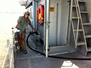 Woman holding fuel hose while fueling a boat