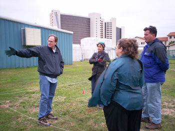 Four sanctuary staff standing in a grassy field discussing boat layout.