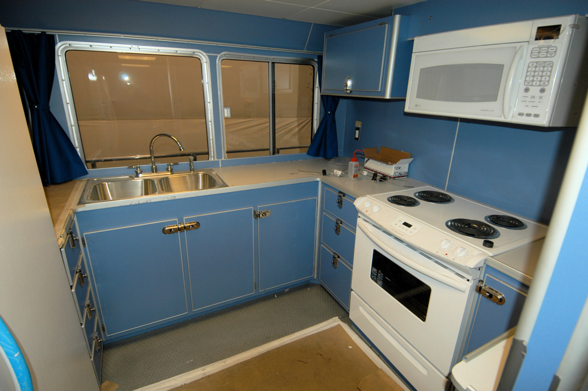 and white microwave oven visible All of the cabinets are light blue