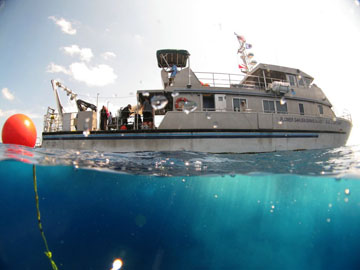 R/V MANTA as seen from the water by a diver at the surface. Below the vessel is turquoise blue water.