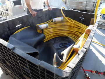 ROV umbilical cable coiled in a large box on the boat deck