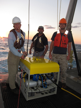 Three-man crew standing around ROV on the deck of a boat
