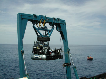 A one-person submersible suspended from a crane.