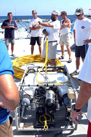 A Phantom S2 ROV on the back deck of a ship with 5 scientists standing behind it.  The scientist in the center is holding on to the umbilical line of the ROV and pointing to the left.