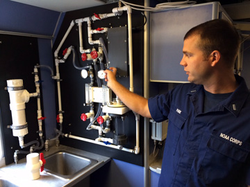 Man pointing out features of a system of water pipes and gauges mounted on the wall above a sink on R/V MANTA