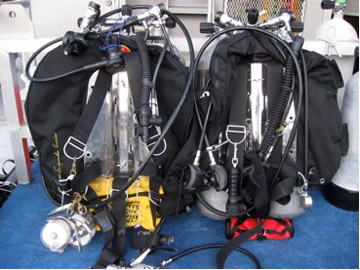 Scuba gear attached to dive tanks sitting on the dive bench on the back deck of the R/V Manta.