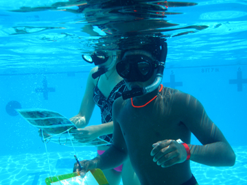 Underwater view of two students in snorkel gear. One is carrying coral ID pictures and the other is carrying a clipboard