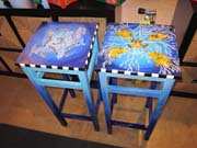 Two wooden stools painted with images of fish from the sanctuary