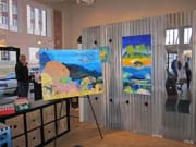 Colorful paintings of marine life on display in a shop.