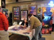 A woman seated at a table autographing posters while other people look on.  Colorful artwork is on display behind her.