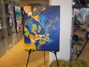A large painting of two weedy seadragons on a bright blue background.  The painting is standing on an easel.