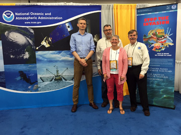 3 men and a woman standing between a NOAA backdrop and a Stop the Invasion lionfish banner in an exhibit booth of a conference hall