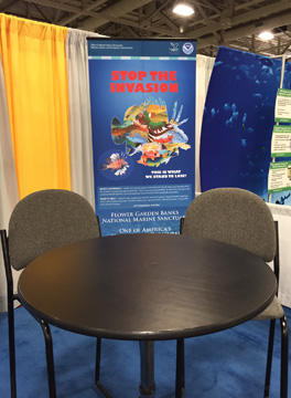 A small table with 2 chairs in front of a Stop the Invasioni banner with the outline of a lionfish filled with images of other fish lionfish have been eating
