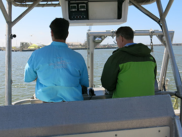 Looking at two men with their backs to the camera as they look at the stern controls of R/V MANTA on the upper deck..