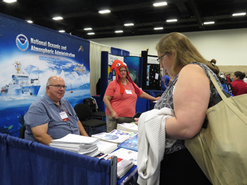 Dennis Cain sitting and Shelley DuPuy standing behind the information tables of the NOAA Education booth while a teacher looks at the selection of materials available.