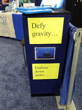 Signs in the NOAA display booth: Defy gravity...Explore down under...