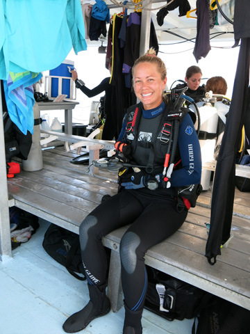 Teacher in full scuba gear sitting on a bench on the dive boat