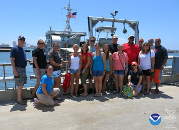 Group of people posing for a photo on the top deck of a dive boat as it returns to shore.