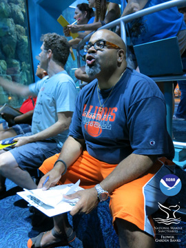 Teachers sitting on a bench with others standing behind them as they look at a large aquarium full of fish.