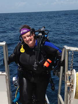 A smiling diver climbing up the ladder onto the boat after a dive.