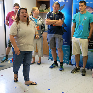 Jennifer standing in the middle of a room with teachers circled around her as she explains a game