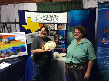 Shelley DuPuy (right) and her sister (left) standing in front of the sanctuary display booth
