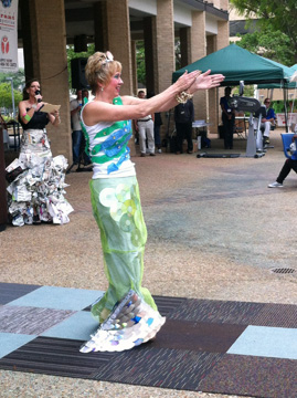 A woman dressed as a mermaid in a costume made from recycled CDs