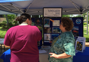 Shelley DuPuy talking to a visitor in front of the sanctuary display booth