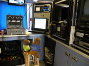 A plush bear toy sits on a stool with a plush sea lion toy in front of all the controls for a remotely operated vehicle.  The controls occupy 3 large cases sitting on a countertop.