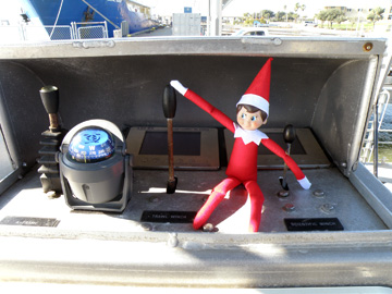 Elf doll sitting at the winch controls of R/V MANTA with his hand on the Trawl Winch control.