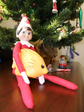 Elf doll holding a foam fish in his lap under a Christmas tree.