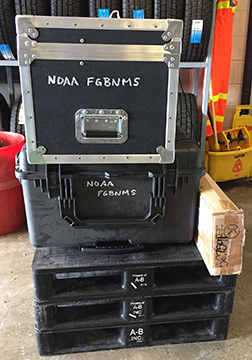 End view of two cases stacked on top of three pallets. Each case is labeled NOAA FGBNMS