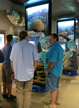 Three men standing in front of the Flourishing but Fragile section of the traveling exhibit.