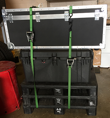 Two black cases strapped on top of three black pallets with a pair of green ratchet straps.