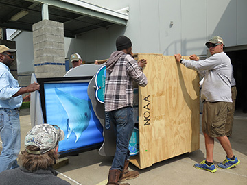 Four men moving a crated exhibit piece on its side