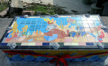 The top of the bench features a tiled design showing tropical reef fish, sea horses, and corals