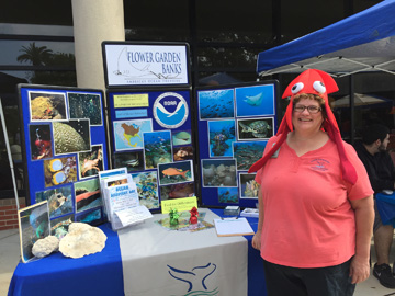 Woman wearing a red squid hat standing in front of a sanctuary display table outside a building