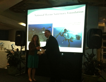 Michelle being handed an enveloped in front of a screen that says National Marine Sanctuary Foundation