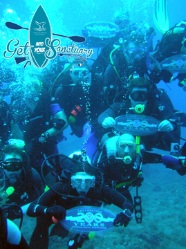 Group of divers posing underwater with signs that say Celebrating 200 Years of NOAA. Get Into Your Sanctuary logo in corner.