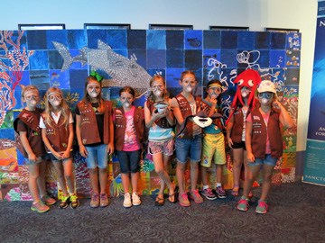 Nine Brownie Girl Scouts pose in their uniforms in front of a sanctuary mural. All are wearing paper scuba masks and one is wearing a red squid hat.